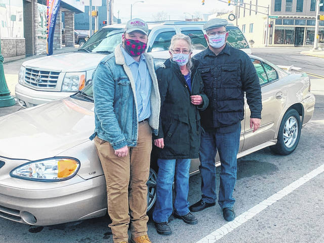 "Zeb Hannan (left) stands with Scarlet Gross (center) and his dad, Pastor John Hannan (right), in front of the vehicle purchased through the ""Operation: Give Love"" campaign at CrossRoads Church, located at 229 W. Pearl Street, in downtown Union City, Indiana."