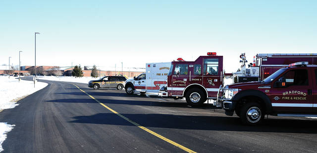 """EMS and fire units from Bradford stand by as Miami County Sheriff's Deputies, with assistance from explosive-sniffing dogs from the Montgomery County Sheriff's Office conduct a search of Bradford School following a """"non-specific bomb threat"""" on Wednesday morning."""