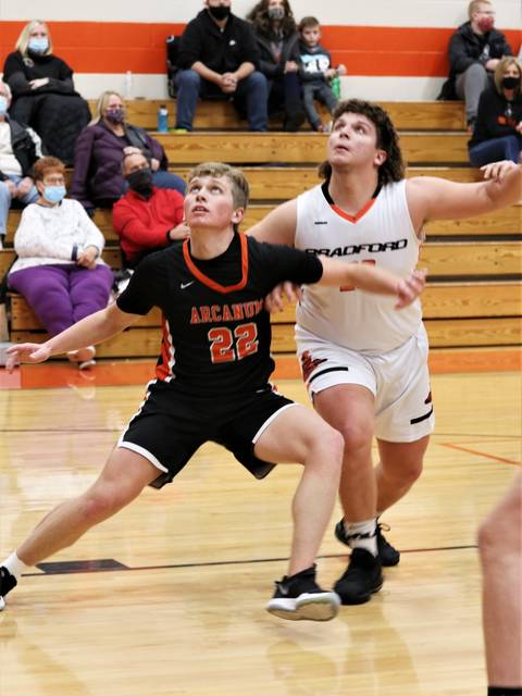 Arcanum's Cameron Burke (22) and Bradford's Gage Wills battle for a rebound in the team's CCC matchup.