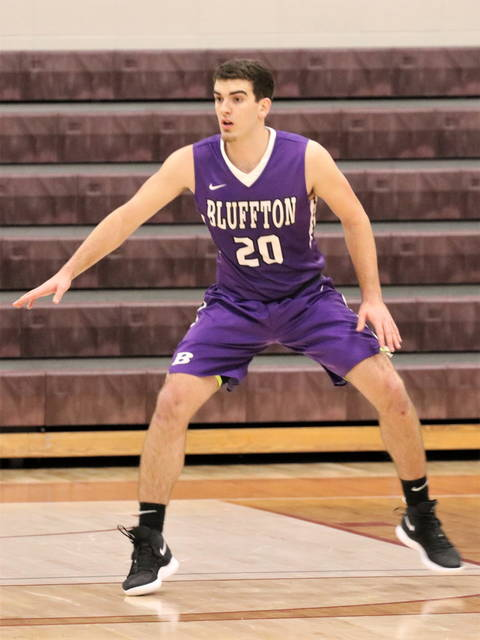 Greenville's Aaron Rich takes up a defensive stance on the road at Richmond's Earlham College.