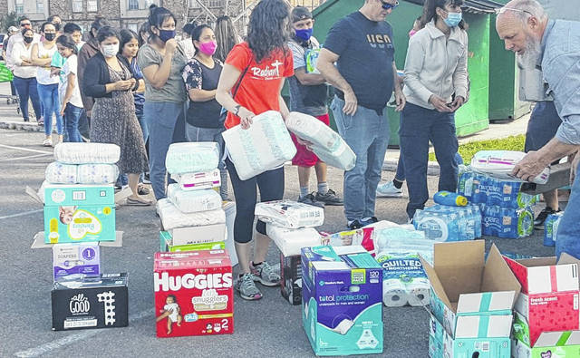 Dennis Garber (right), a semi driver for GTL Transportation in West Manchester, Ohio, is seen passing out water and other supplies to members of Houston's Gulfton neighborhood last Saturday.