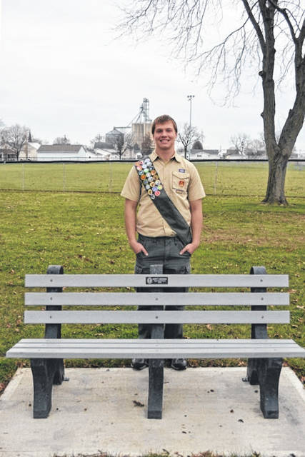 Osgood Eagle Scout Kurt Meiring stands beside one of the four newly installed plastic benches at Osgood Community Park. In addition to collecting over 800 pounds of plastic, Meiring dug the holes, made forms, poured stone and concrete for the 4-foot by 7-foot slabs, and raised over $1300 to help fund the project. He is a member of Maria Stein Boy Scout Troop # 97.