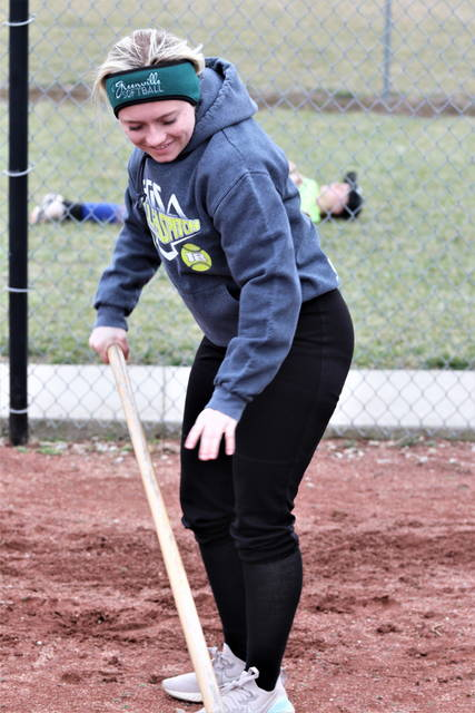 Greenville senior pitcher, Grace Shaffer manicures the pitching cage following team's practice.