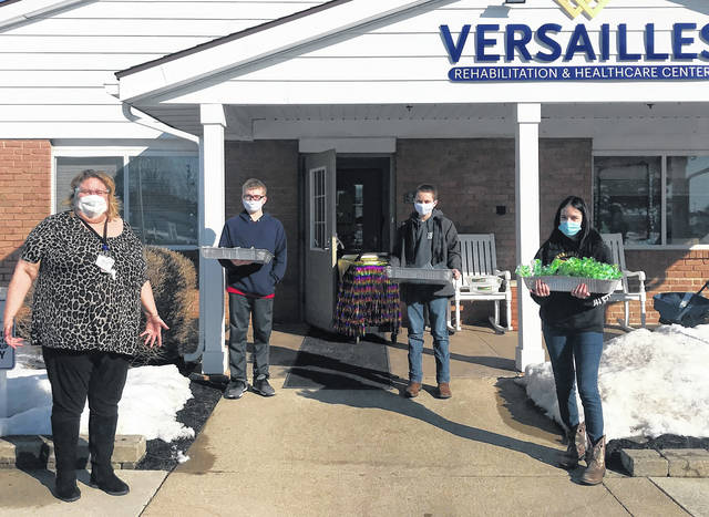 Versailles FFA members are seen at the Versailles Health Care Center on Feb. 23 with Kim Fair, Activities Director of Versailles Health Care Center staff. Versailles FFA members that assisted included left to right: Owen DeMange, Jeremiah Wagner and Haylee Lewis. Versailles FFA dropped off craft bags and snacks for staff and residents.