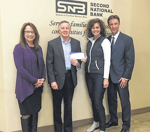 Park National Bank's Joy Greer and John Swallow present a check to Kelly and Travis Fliehman for the April 9 Red & Yellow / Black & White Gala.