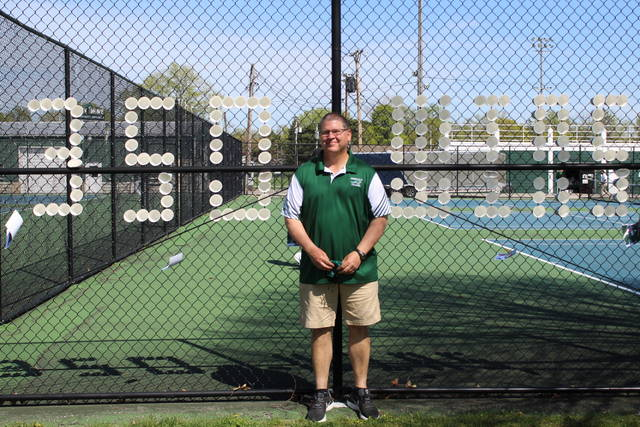"""Green Wave boys tennis coach, Dennis Kiser stands in front of tennis courts with """"350 wins"""" embedded in the fence made from styrofoam cups."""