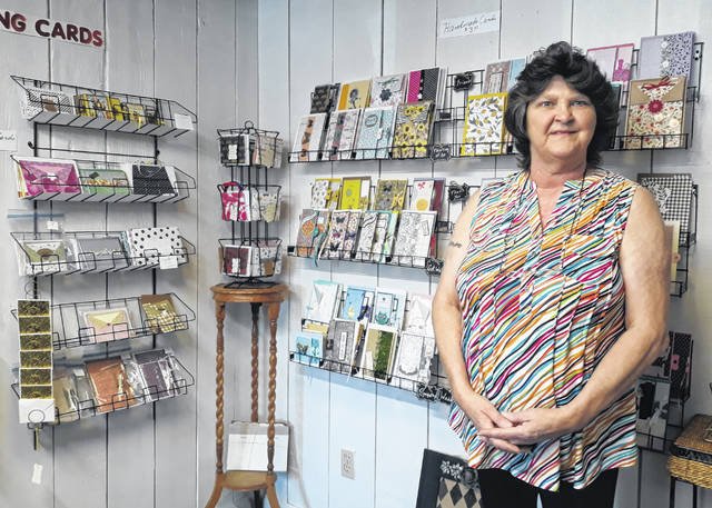 "Christina Nestor (pictured) stands next to a display of her hand-crafted, ""one of a kind"" cards. Nestor is the owner of Nestor's Nook, located at 144 W. Fourth Street (the corner of Sycamore and Fourth Street) in downtown Greenville."