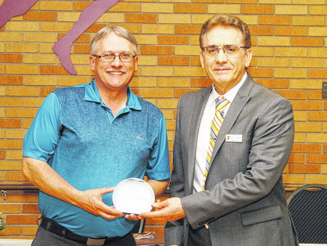 Darke County YMCA CEO Sam Casalano, right, presents Board Member Denis Short with the Y's Volunteer of the Year Award for 2020 during the Y Annual Meeting held Thursday evening.