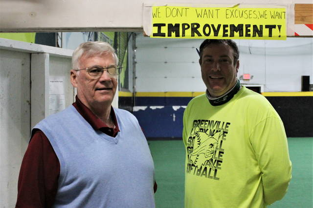 """Mike Stegall and Coach Jerrod Newland stand under motivation sign at the Academy - """"We don't want excuses, we want IMPROVEMENT!"""""""