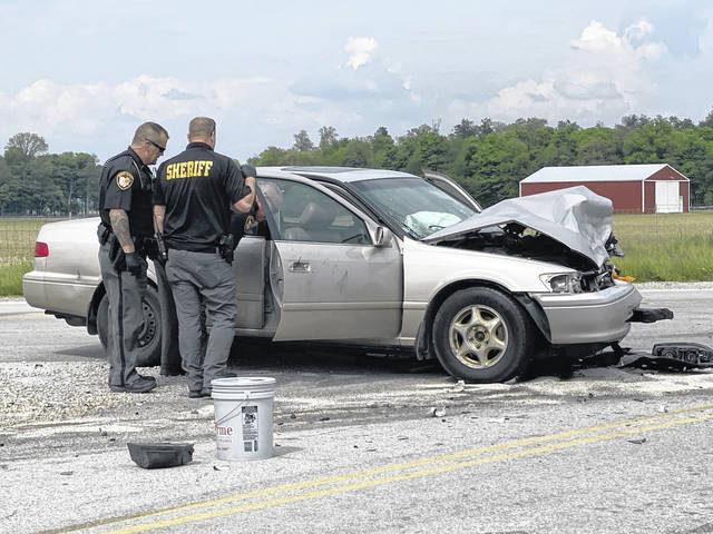 Darke County Sheriff's deputies are shown at the scene of a head-on collision Wednesday near Arcanum. The driver of one vehicle was arrested on a felony warrant out of Montgomery County.