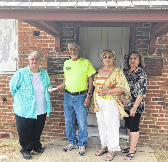 Fort GreeneVille Chapter of the Daughters of the American Revolution Regent Brenda Arnett (left) stands with Tom Lucas, and Historical Preservation Chapter Committee members Karen Burkett and Debbie Nisonger at the entrance of the Studabaker Schoolhouse, located 5335 Heritage Road (St Route 49 S) in Greenville.
