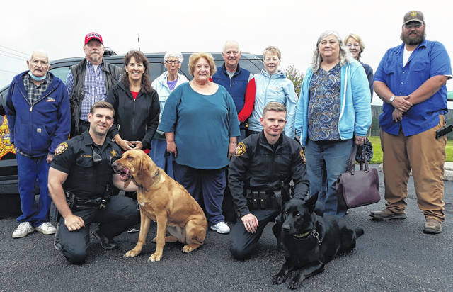 Darke County Friends of the Shelter stand with Darke County Deputy Tyler Young and K9 Officer, Annie (front, left), and Darke County Sheriff's Deputy Colton Magel and K9 Officer, Bear (front, right).