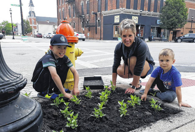"""Mainstreet Greenville Planting Day organizer, Hillary Holzapfel (center), plants with sons, Graham, age 10 (left) and Trey, age 4 (right). Groups or persons wishing to """"adopt a flower bed"""" to water once a week on Broadway, contact 937-417-3161."""