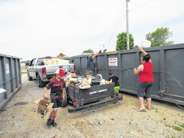 Jalen Lester (front) helps parents Cody and Kaelyn Lester, and little brother Jalen, unload trash emptied from his late grandfather's house during Union City's annual cleanup weekend.