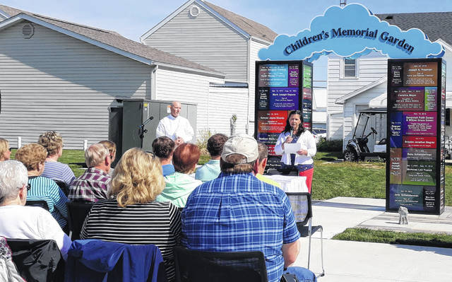 Karen Homan, founder of Do Good Restaurant and Ministry, welcomes families, friends and attendees to the dedication of the Children's Memorial Garden, located at 25 West Main Street in Osgood, Ohio.
