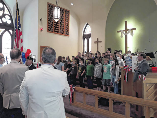 The Greenville American Legion Post 140 Color Guard stand with the flag, while the Decolores Montessori School fourth, fifth and sixth grade students sing the National Anthem at the 70th annual National Day of Prayer.