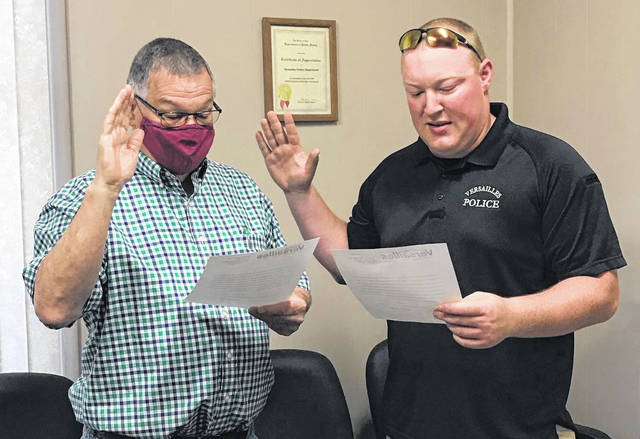 Versailles Councilman Mike Berger (left) swears in Officer Shane Grieves (right), the newest member of the Village of Versailles Police Department.