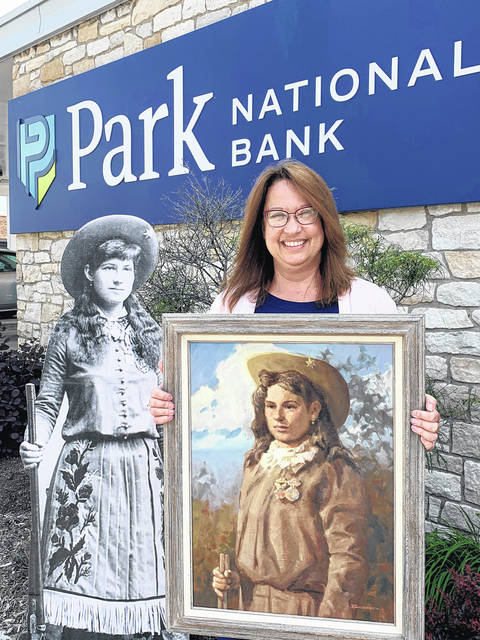 Two Annie's and a Joy! Recognizing the ongoing Annie's G.A.L.A. (Garst Alternative to Live Auction) is Park National's Joy Greer, Retail Banking Administrator, shown with Annie and one of several paintings by the late famous artist Bob Brubaker donated to Garst Museum by Park National Bank for the Silent Auction.