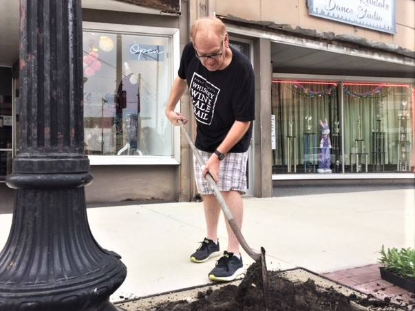 Ryan Berry, Executive Director Main Street Greenville lends a hand to Adopt-A-Box with beautifying Downtown Greenville.