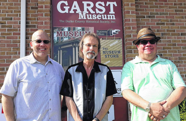 Entertainers David Burris and Greg Bell stand with board member Perry Walls (right) at the entrance to the Garst Museum during the Annie's G.A.L.A. tail-gate and drive-thru on Saturday.