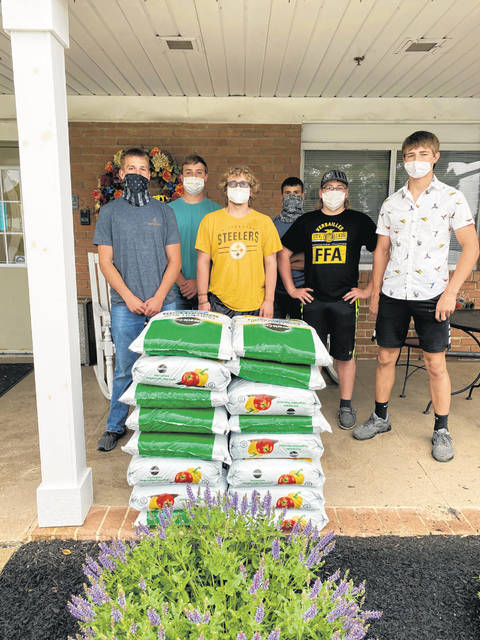 Versailles FFA members left to right: Ayden Bergman, Isaiah Hess, Alex Mangen, Alex Dircksen, Austin Spradlin and Caleb Kaiser are shown at the Versailles Health Care Center delivering the remaining soil donated by Versailles Ace and Eric Biggs State Farm Agency.
