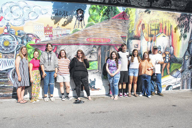 In collaboration with the Ohio Arts Council and visiting artist Timothy Wells (far left), Mississinawa Valley Schools teacher Ashley Austerman (far right) and her students unveiled the large mural they've worked on for an entire semester.