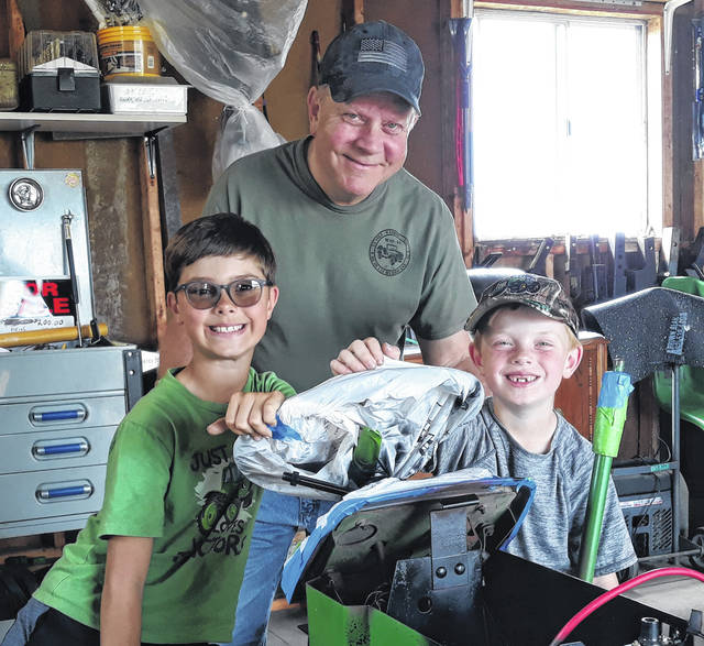 Ten-year-old Jensen Detro (left) is all smiles standing next to his Grandpa, D'Kim Detro, little brother Ezra Detro (age eight), and the 214 Model 1977 John Deere Garden Tractor they are fixing up together.