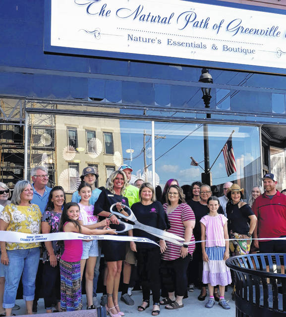 Surrounded by family and friends, Sarah Royer, (center), owner of The Natural Path, cuts the ceremonial ribbon to open The Natural Path's second downtown Greenville location at 402 S. Broadway.