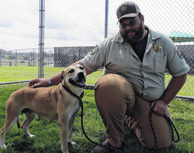 """Darke County Animal Shelter Director and Dog Warden, Robert Bair strikes a pose with Shelby, a current canine resident hoping to be adopted at the Shelter's """"Open House,"""" taking place on Saturday, July 24, from 12 to 3 p.m. Fun, food, prizes, pet photos and $25 microchipping are some of the events in store. Visit the shelter's on Facebook at www.facebook.com/ohiodcas."""