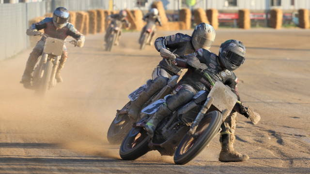 Flat track motorcycle racers pass by the grandstand at the Darke County Fairgrounds.