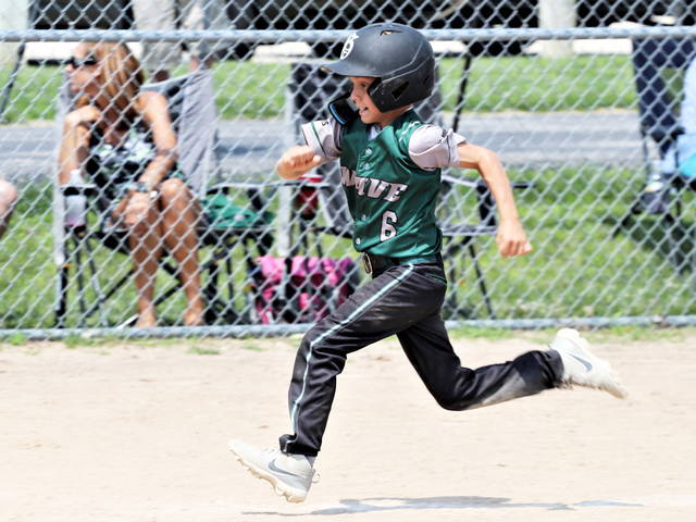A young tournament player races home in at the Annie Oakley Classic baseball tournament.