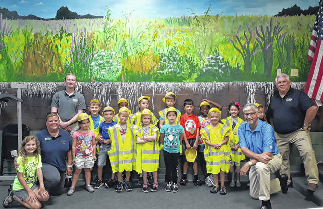 """Young geologists from the Darke County Parks' """"Camp Rocks"""" summer program are joined by Mandy Martin (left), Kasey Damewood, of Piqua Minerals (back row) Pat Jacomet, Executive Director of the OAIMA (right), and Dave Groth, Sales Rep for Piqua Materials in Piqua, Ohio (right, outside)."""