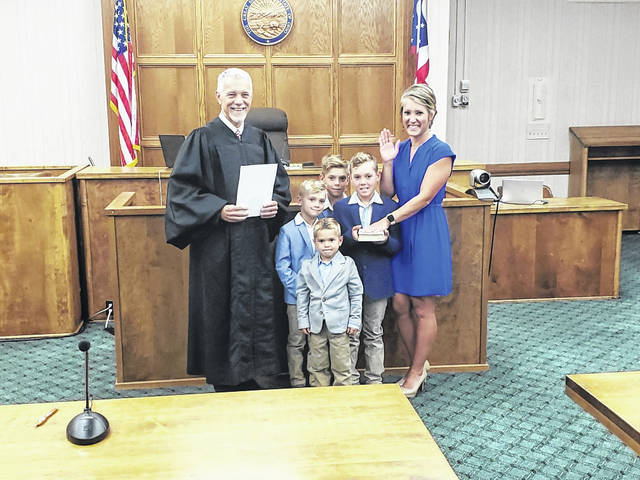 Hillary Holzapfel was sworn in as Darke County Recorder on July 2. Shown at her swearing-in ceremony are Judge Jonathan P. Hein, Holzapfel, and her four sons.