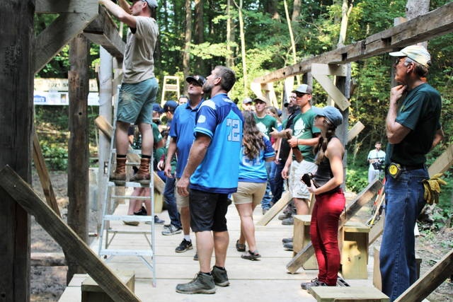 Matt Light looks on as campers and crew work on timber frame covered bridge at Chenoweth Trails.