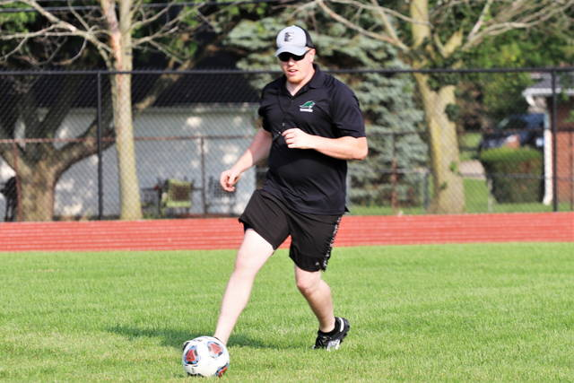 First year Greenville head varsity football coach, Marshall Combs demonstrates a move at the team's voluntary workout.