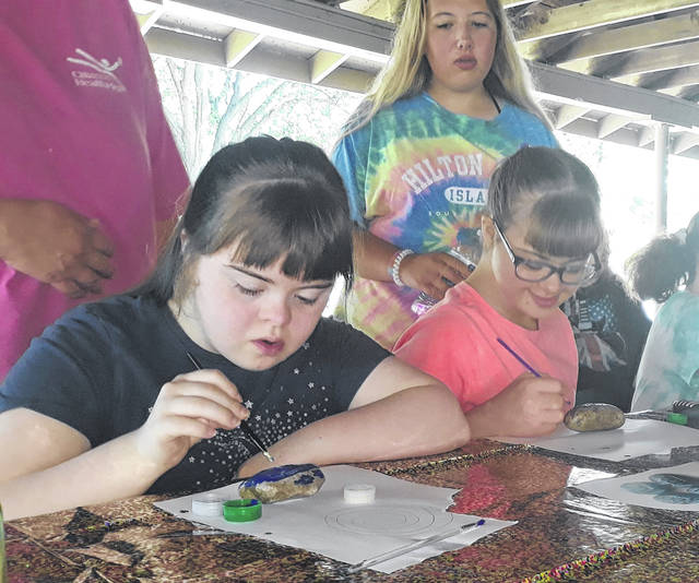 """(Left to right) Aktion club members Chloe Brodrick, Mary Anne Whittaker, and sister, Alyssa, concentrate on painting during the """"Kindness Rocks"""" event which happened Tuesday, June 30, sponsored by the Greenville Kiwanis Aktion Club and Darke County's We Are the Majority."""