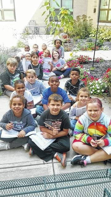Ms. Hamilton's class at Wright Brothers Elementary took advantage of the wonderful September weather to get outside and practice their cursive writing. Mr. Sanders, Wright Brothers' custodian, maintains the courtyard so beautifully that the students love the opportunity to sit in the flower garden while practicing their writing.