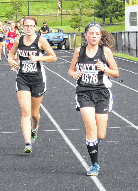 Brooklyn McFadden and Kyrsten Childress run at the Greater Western Ohio Conference championships in Centerville on Saturday.