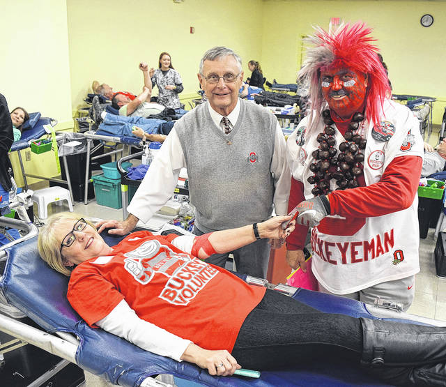 "Huber Heights resident Dennis ""Tress"" Singleton and ""Buckeyeman"" Larry Lokai greet donor Helen Ward at the Shelby County Ohio State University Alumni Association blood drive."