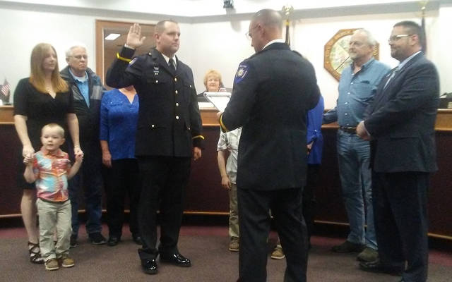 Huber Heights Police Chief Mark Lightner swore in new Police Sgt. Brian Carr while members of Carr's family and Mayor Jeff Gore watch during Monday's City Council meeting.