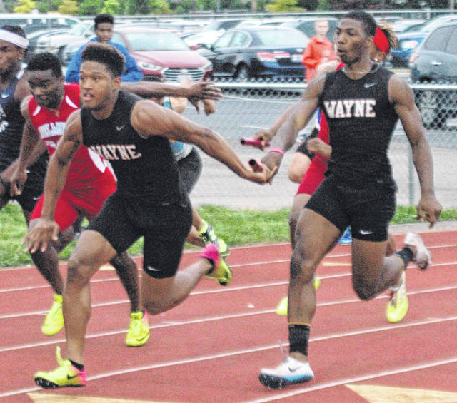 <strong>Justin Harris hands the baton to Zarik Brown on the final leg of the 4x100 meter relay. Wayne won the event with a time 42.08 seconds.</strong>