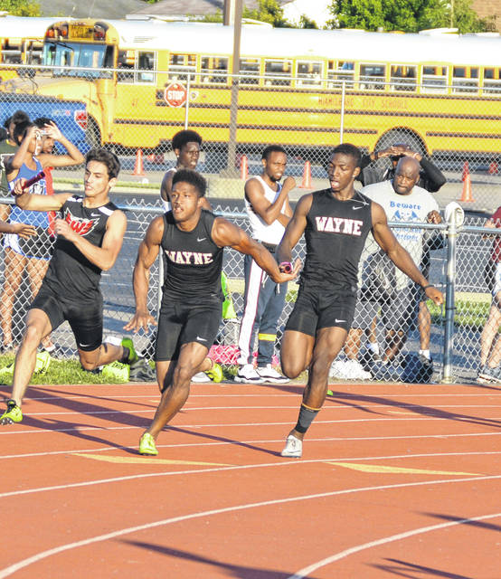 <strong>Justin Harris hands the baton to Zarik Brown on the final leg of the 4x100 meter relay.</strong>