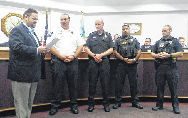 Huber Heights Mayor Jeff Gore reads a proclamation for National Police Week at Monday night's council meeting. Representing the Huber Heights Police Department are Tom Milligan, Ed Savard, Dorian Ringer and Andy Blankenship.