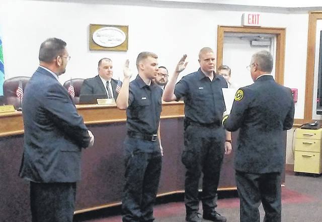 Huber Heights Fire Chief Mark Ashworth swore in new firefighters/paramedics Jack Jacobsen amd Matthew Kuntz at the beginning of the Huber Heights City Council meeting on Monday, June 11 as Mayor Jeff Gore looks on.
