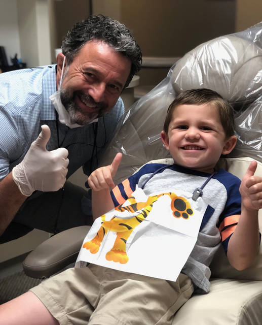 Dr. Chris Kondas, pictured with his patient Cooper, along with Dr. Jonathan Wells and volunteers from Kondas Dental Group will be offering free dental checks, teeth cleaning, flouride, and dental education during Give Kids A Smile on August 18. Call 236-2800 for an appointment.