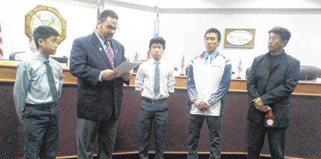 Mayor Jeff Gore reads a proclamation honoring Huber Heights residents Derikson, Spencer and Vincent Meng honoring them for their accomplishments at recent national and international martial arts competitions.