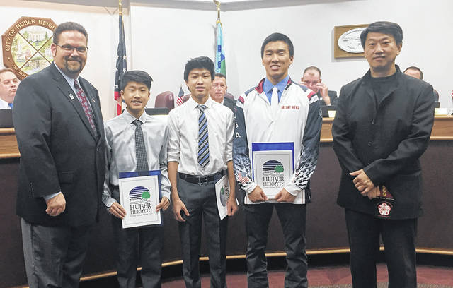 Huber Heights Mayor Jeff Gore reads a proclamation honoring Huber Heights residents Derikson, Spencer and Vincent Meng honoring them for their accomplishments at recent national and international martial arts competitions.