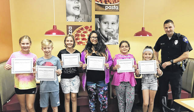 Pictured are the September Safety Patrol of the Month awardees Kennedy Reeser and Tyler Knueve from Wright Brothers Elementary, Claire Todd and Ashlynn Holland from Monticello Elementary, Cheyenne Mahaffy and Avalon Sparks from Rushmore Elementary. They are pictured with School Resource Officer and Huber Heights Police Officer Nick Lambert.