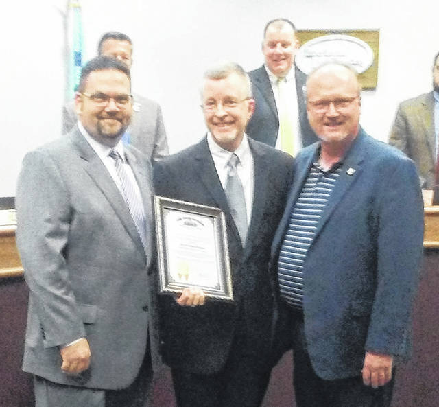 Joe Braden of the Ohio auditor's office presents the Ohio Auditor of State's Award with Distinction to Mayor Jeff Gore and Director of Finance James Bell.