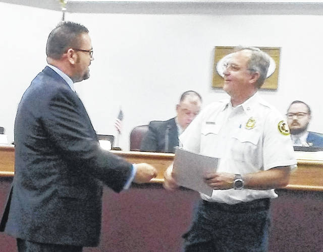 Huber Heights Mayor Jeff Gore presents a proclamation to Fire Chief Mark Ashworth declaring October as Fire Prevention Month during the city council meeting on Monday, Sept. 24.